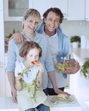 Young girl eating carrot with parents Stock Image