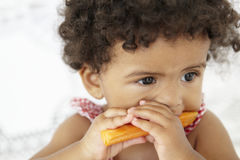 Young Girl Eating Carrot Stick Stock Image