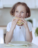 Young girl eating cheese sandwich Stock Photos