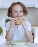 Young girl eating cheese sandwich stock image