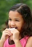 Young Girl Eating Chocolate. Young girl outside eating a candybar Royalty Free Stock Image