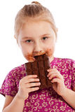 Young girl eating a chocolate bar. Royalty Free Stock Photography