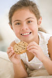 Young girl eating cookie in living room smiling. At camera Stock Images