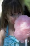 Young girl eating cotton candy. Young brunette girl eating cotton candy at the park Royalty Free Stock Images
