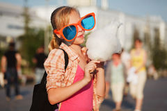 Teen girl in sunglasses eating cotton candy on city street Royalty Free Stock Photos