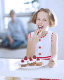 Young girl eating cup cake Royalty Free Stock Photography