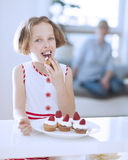 Young girl eating cup cake Royalty Free Stock Images