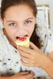 Young girl eating cupcake Stock Photography
