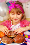 Young girl eating donuts on party Royalty Free Stock Images