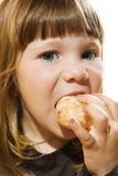 Young girl eating a doughnut Royalty Free Stock Photography