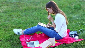 Young girl eating fast food and enjoys the tablet, thinking. Beautiful woman sitting on a blanket and eating fast food fries. Lady with long brown hair wearing stock video