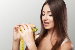 Young girl eating food, burger fast food, American unhealthy die. Tary calorie Concept of health and beauty On a gray background Royalty Free Stock Image
