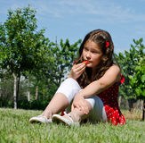 Young girl eating a fresh strawberry Royalty Free Stock Photography