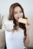 Young girl is eating fresh toast holding a glass of milk Royalty Free Stock Image