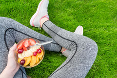 Young girl eating a fruit salad after a workout . Royalty Free Stock Photography