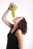 Young girl eating grapes. A young girl eating a big bunch of grapes Royalty Free Stock Photo