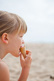 Young girl eating ice cream on beach Royalty Free Stock Photography
