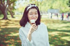 Young girl is eating ice cream and happy. At the time of relaxation. stock image