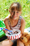Young girl eating ice cream on the picnic. Young girl eating big ice cream in box sitting on the blanket on the picnic Royalty Free Stock Photo