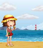 A young girl eating an icecream at the seashore Stock Images