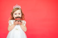 Young girl eating mini birthday cake over red background Royalty Free Stock Images
