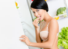 Young girl eating near the opened fridge Stock Photo