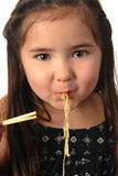 Young girl eating noodle soup Royalty Free Stock Image