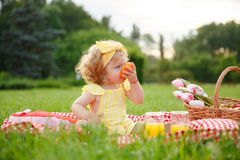 Young girl eating orange sitting on blanket Royalty Free Stock Images