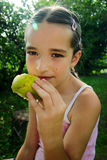 Young girl eating pear outdoor Royalty Free Stock Images
