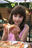 Young girl eating pizza. Beautiful young girl preparing to take a bite from a pizza slice Stock Images