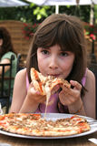Young girl eating pizza. Beautiful young girl preparing to eat a slice of pizza Royalty Free Stock Images