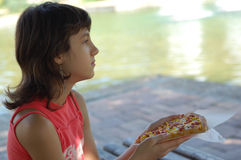 Young girl eating pizza royalty free stock image