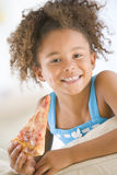 Young girl eating pizza slice in living room. Smiling Stock Photos