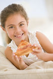 Young girl eating pizza slice in living room Royalty Free Stock Photos