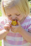 Young girl eating a plum royalty free stock photos