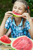 Young girl eating ripe watermelon Stock Photos
