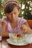 Young Girl Eating Salad Stock Image