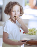 Young girl eating salad whilst holding knife in kitchen Royalty Free Stock Images
