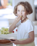 Young girl eating salad whilst holding knife in kitchen Stock Image
