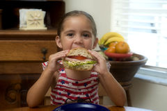 Young girl eating sandwich in hand royalty free stock photo