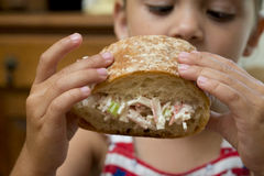 Young girl eating sandwich in hand royalty free stock photos