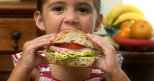 Young girl eating sandwich in hand looking at camera stock image