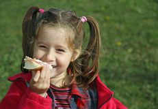 Young girl while eating the sandwich Royalty Free Stock Photos