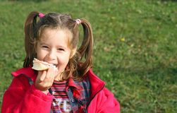 Young girl while eating the sandwich, smiling Stock Images