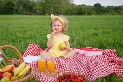 Young girl eating sitting on blanket outside Stock Images