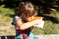 Young girl eating a slice of cheese pizza outside. Young girl eating a slice of cheese pizza Royalty Free Stock Photos