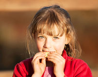 Young girl eating slice of cucumber Stock Image