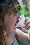 Young girl eating a snow cone. Young brunette girl eating a snow cone Stock Photo
