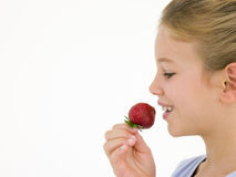 Young girl eating strawberry Royalty Free Stock Photography