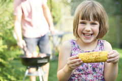 Young Girl Eating Sweetcorn At Family Barbeque Royalty Free Stock Images